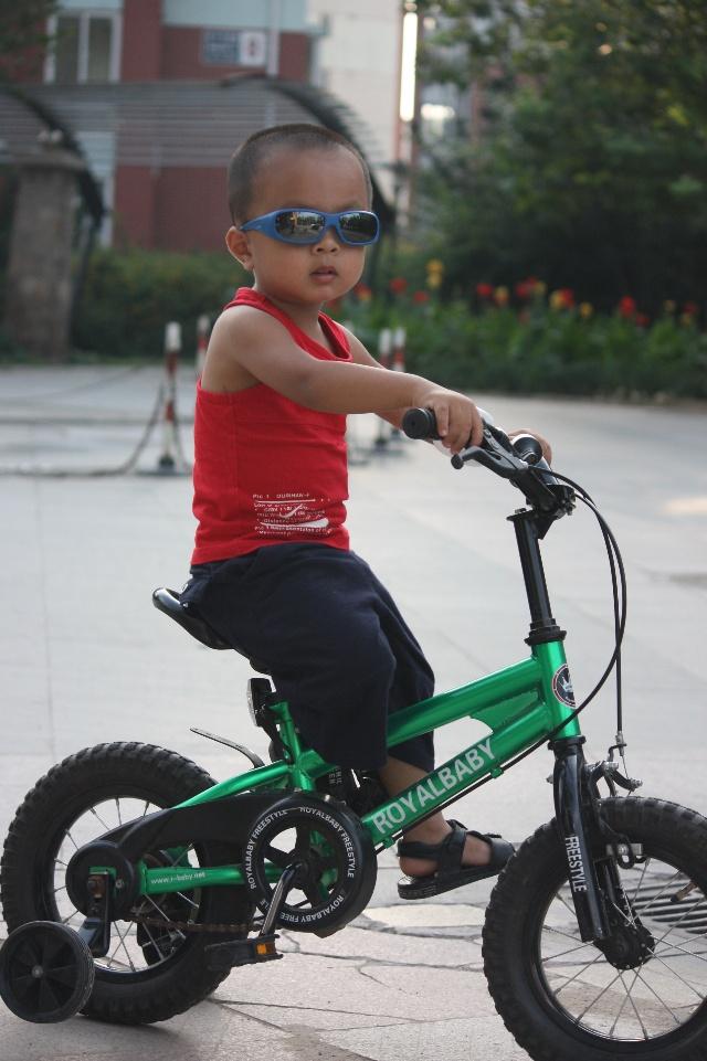 夕阳西下·戴墨镜骑自行车的小男孩