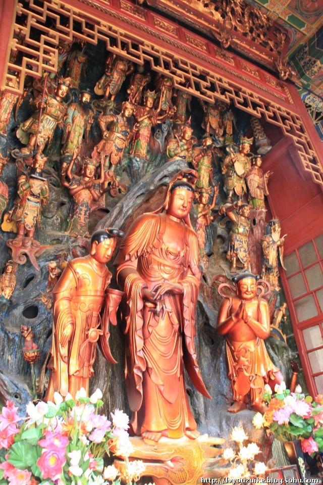 海岛观音赤足站立,左右侍立着龙女和童子,背后是一面高达八尺的泥塑悬